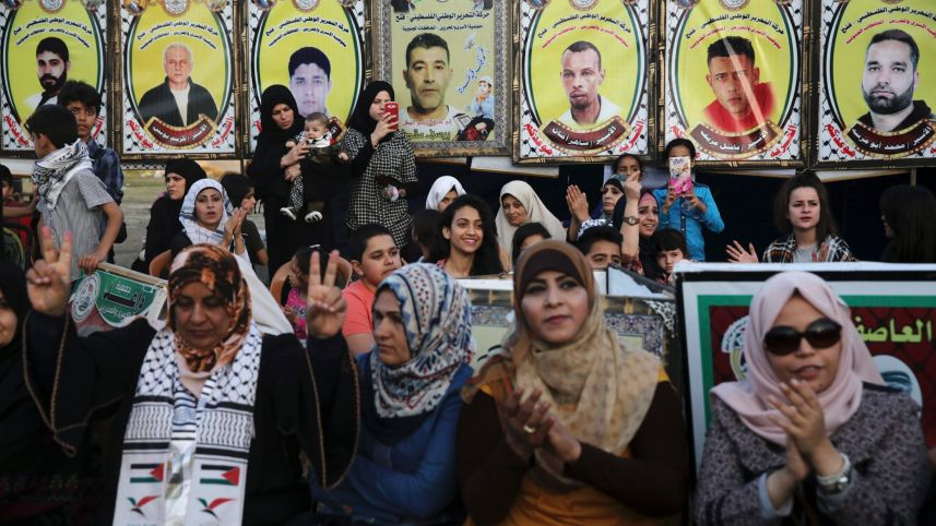 File photo: Women sit in front of photographs of jailed hunger-striking Palestinian prisoners in Gaza city, May 4, 2017. Adel Hana/AP