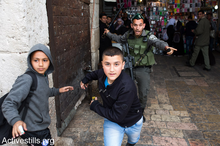 Israeli border police officer chases Palestinian children during land day demonstration in Damascus gate, East Jerusalem, March 30, 2014.