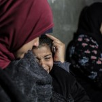 Hala al-Najjar, 38, holds her daughter, crying at home in Khan Younis after her son, Bilal, was killed (MEE/Sanad Abu Latifa)