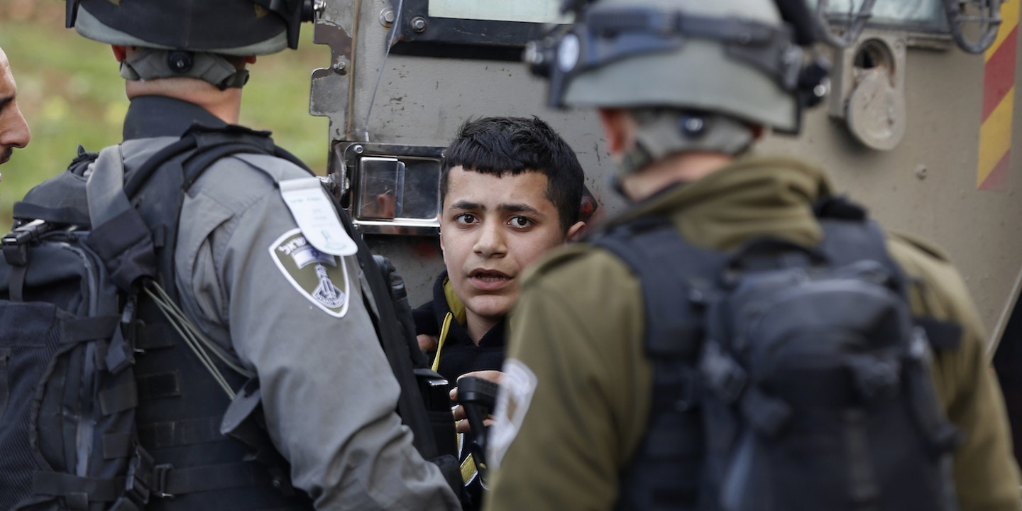 Israeli officers arrested a Palestinian boy during a 2017 protest outside an Israeli military prison in the occupied West Bank. Photo: Majdi Mohammed/AP