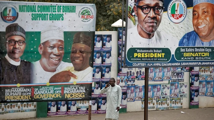 File photo: A man takes a call as he stands between two billboards showing Nigeria's President Muhammadu Buhari and other party officials, in Kano, northern Nigeria, February 26, 2019.Ben Curtis/AP