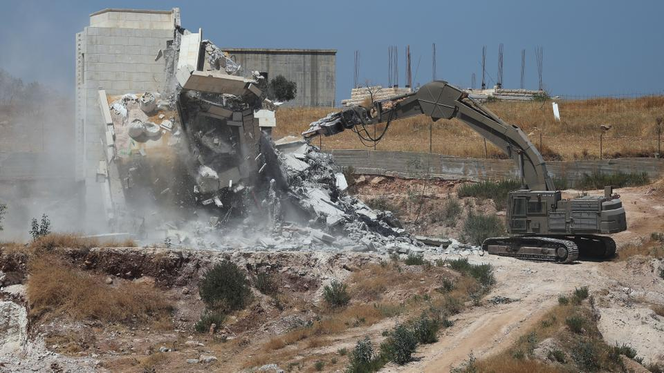 Israeli military machinery demolishes a Palestinian building in the village of Sur Baher which sits on either side of the Israeli barrier in East Jerusalem and the Israeli-occupied West Bank on July 22, 2019. (Reuters)