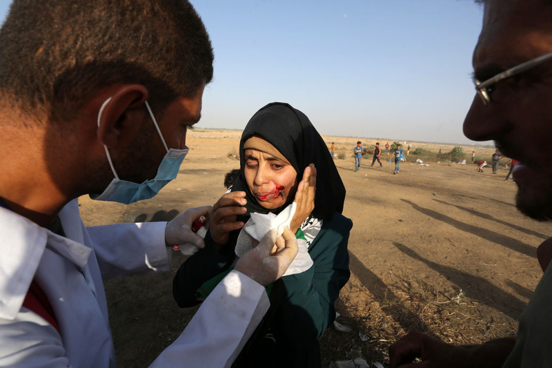 A protester is treated by paramedics during Great March of Return protests in Khan Younis, southern Gaza Strip, on 12 July. Ashraf Amra APA images)