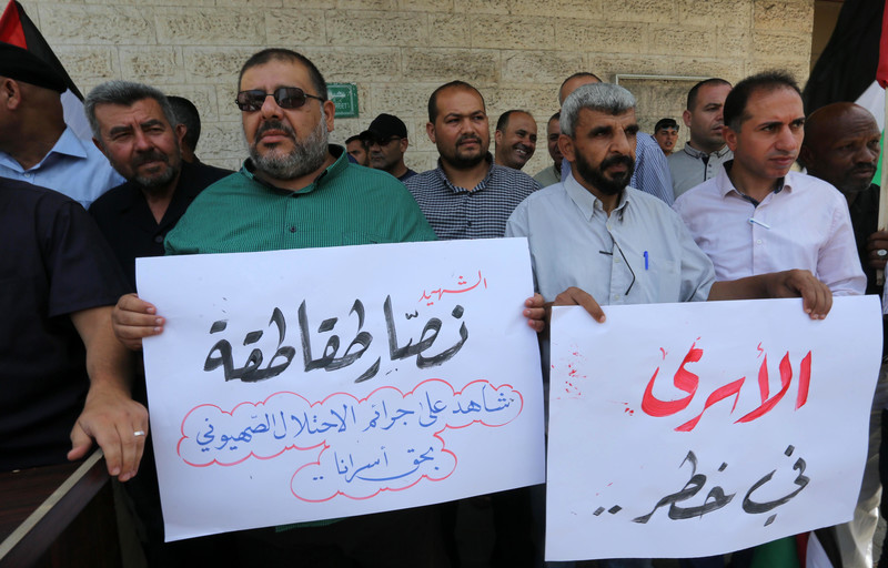 Palestinians protest the death of Nassar Taqatqa in Israeli prisons, in front of the Red Cross building in Gaza City on 16 July.  Ashraf Amra APA images