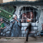 A man passes a mural supporting Palestinian prisoners in Israeli jails, in the West Bank city of Ramallah, Thursday, April 27, 2017. Palestinians across the West Bank are observing a general strike in support of hundreds of hunger-striking prisoners held by Israel. Palestinians say between 1,300 and 1,500 prisoners have been on a hunger strike for 11 days, demanding better conditions and more contact with relatives. (AP Photo/Nasser Nasser)