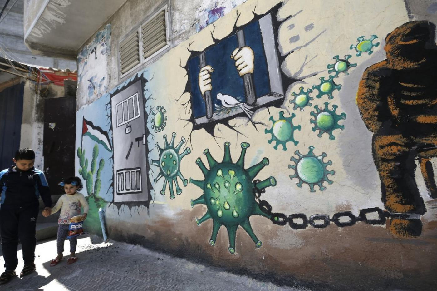 Palestinian children walk past a mural depicting the coronavirus and a prison cell in Gaza City on 28 April (AFP)