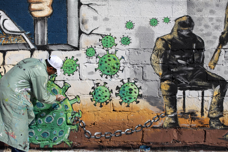 An artist in Gaza City paints a mural in support of Palestinians held in Israeli jails during the COVID-19 pandemic, on 20 April. Mahmoud AjjourAPA images