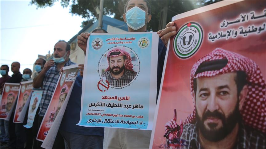 Protesters from Prisoners' Committee of the National and Islamic Forces hold posters of Maher Al-Akhras, who has been on hunger strike for 73 consecutive days in Israeli jail, during a protest demanding release of Maher Al-Akhras in front of the United Nations High Commissioner for Human Rights office building in Gaza City, Gaza on October 07, 2020. ( Ali Jadallah - Anadolu Agency )