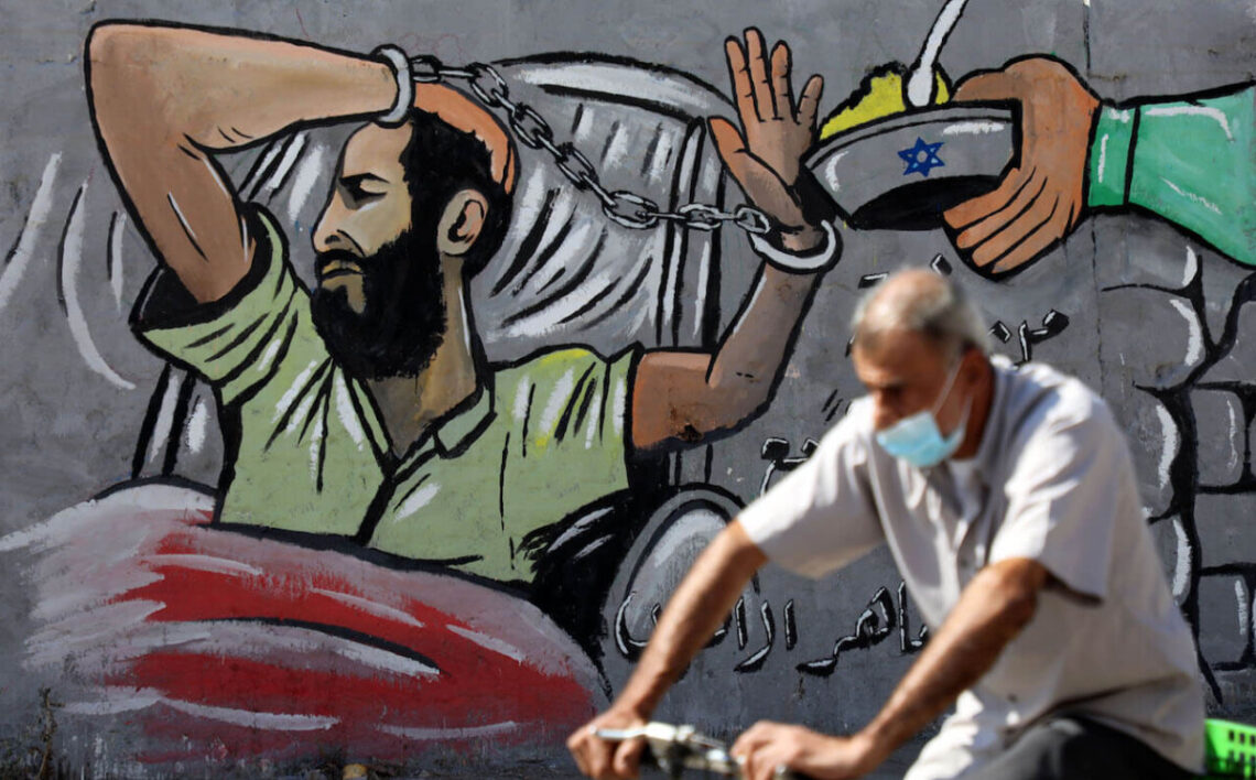 A Palestinian man wearing a protective mask walks past a mural depicting prisoner Maher Al-Akhras, 49, a Palestinian jailed by Israel, who has been on hunger strike for 84 days, protesting his detention without trial, in Gaza City October 18, 2020. Photo by Majdi Fathi / NurPhoto via Getty Images